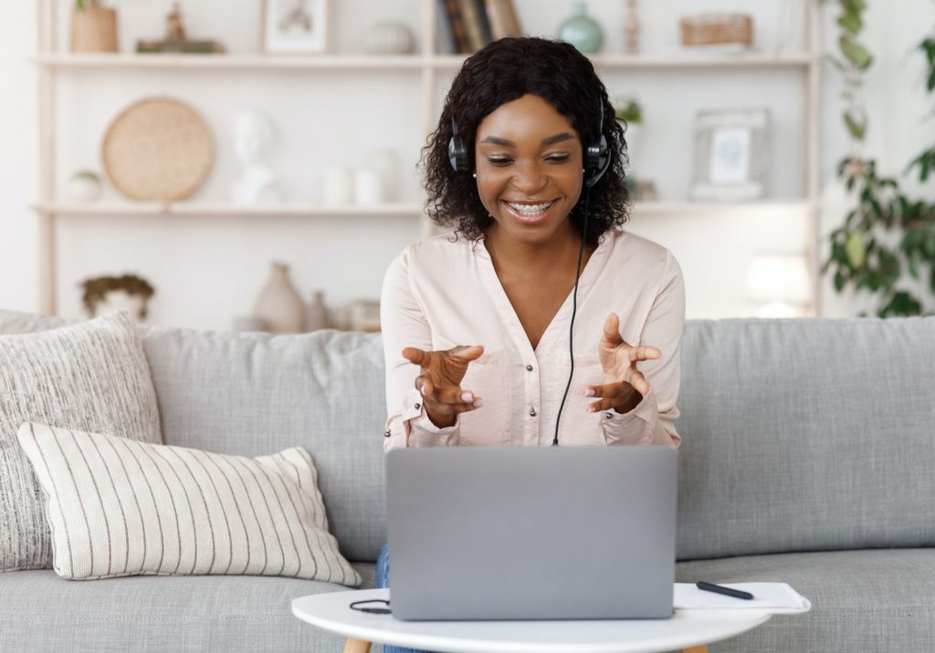 Online Tutoring Concept. Smiling black female tutor having video call with student