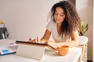 Smiling girl with curly hair sitting at the table with book and cup of coffee dreamily using tablet