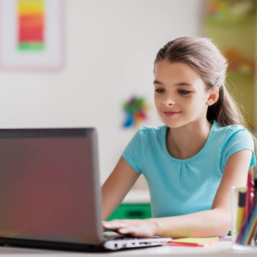 people, children and technology concept - girl typing on laptop computer at home